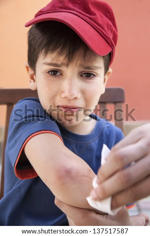 Small boy crying in pain injuring his hand. Father provides first aid - stock photo
