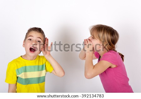 Small boy cupping his ear cant hear his sister shouting - stock photo