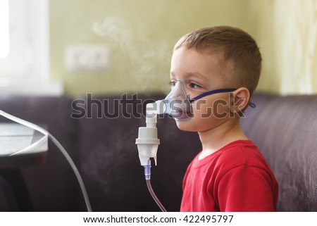 Small boy does therapeutic inhalation using a nebulizer - stock photo