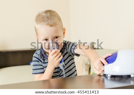 Small boy does therapeutic inhalation using a nebulizer. switch on off a nebulizer - stock photo