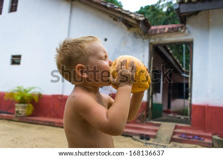 Small boy  drinking coconut milk - stock photo