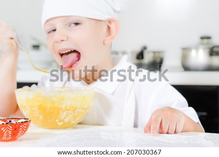 Small boy learning to cook checking his mixture in the mixing bowl against the ingredients in the recipe book - stock photo