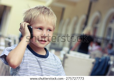 Small boy listening to a mobile phone, tinted photo. - stock photo