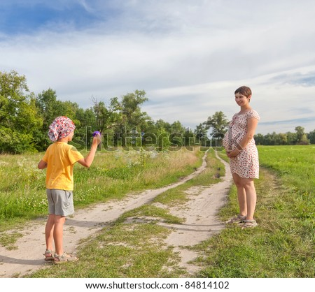 Small boy making soap bubbles with his regnant mother in the green field - stock photo