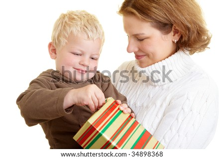 Small boy opening a gift with his mother - stock photo