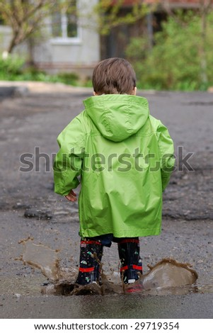 small boy playing in puddles - stock photo