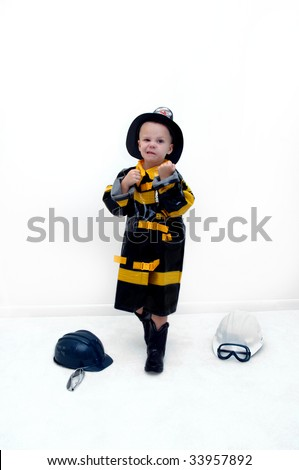 Small boy puts his fists up to help him fight against fire.  He is wearing a fireman's costume and hat.  Two helmets and a pair of goggles lay on the carpet in an all white room. - stock photo