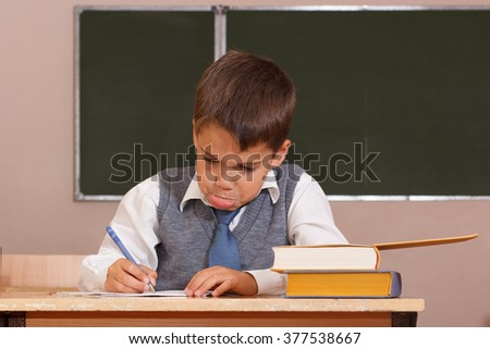 Small boy sitting at a school desk in the classroom experiencing difficulties in their studies . - stock photo