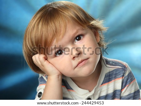 small boy sitting on a chair, looking at the camera, interesting emotions - stock photo