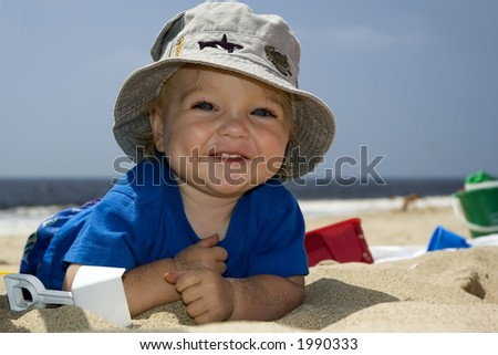 small boy  smiling on the beach with hat and beach toys - stock photo