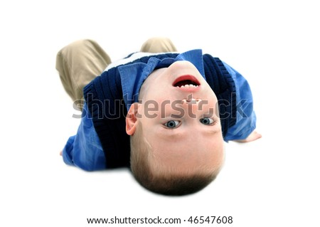 Small boy turns his world upside down to get a different and new view.  He is laying on an all white floor with his head tilted backwards.  He is wearing khakis and navy blue sweater. - stock photo