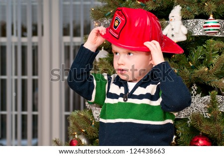 Small boy with a toy fireman hat - stock photo