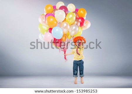 Small boy with bunch of balloons - stock photo