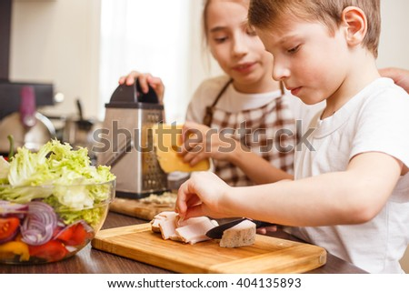 Small boy with his sister preparing food together. Family food cooking together - stock photo