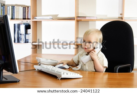Small boy with phone and computer in office - stock photo
