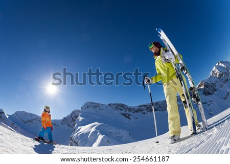 Small boy with woman in mask holding ski and poles - stock photo