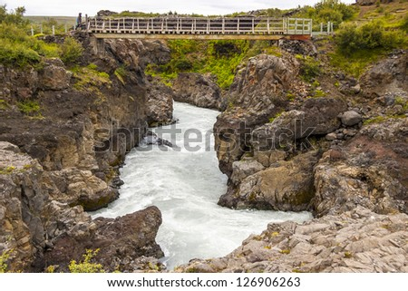 Small bridge on river near Hraunfossar waterfall - Iceland. - stock photo