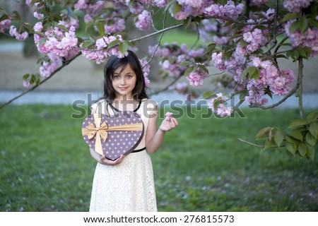 Small brunette smiling girl looking forward holding big brown heart shaped gift box and pink flowers standing among japanese cherry blossom in the park copyspace, horizontal picture  - stock photo