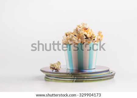 Small bucket of popcorn placed on a stack of movie DVDs. A concept for home theater entertainment. - stock photo
