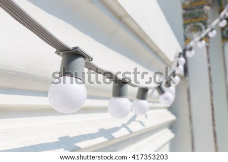 Small bulbs in a row. The walls are white. White bulbs adorn the walls. - stock photo