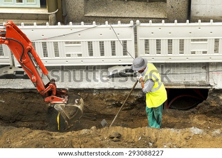 small bulldozer excavator  construction vehicle working for repair pipes in street city - stock photo