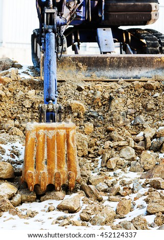 Small bulldozer excavator loader machine works outdoors at construction site. - stock photo