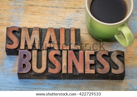 small business banner in vintage letterpress wood type blocks stained by color inks with a cup of coffee - stock photo