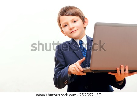 Small business. Cute little boy in tie and formalwear looking out of the laptop and smiling while standing against white background with copy space - stock photo