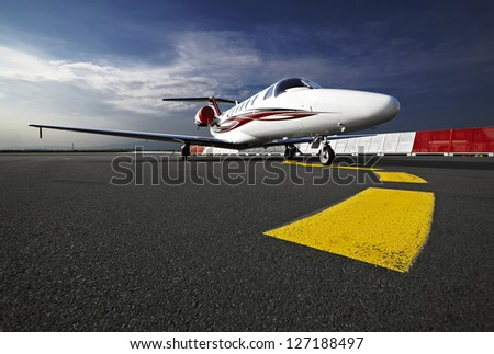 Small business jet plane on a runaway - stock photo