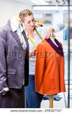 Small business owner dressing shop window putting new fashion clothes on mannequin - stock photo