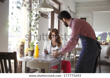 Small business owner serving coffee and cookies in coffee shop. - stock photo