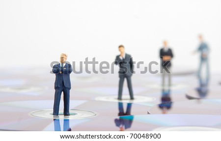 Small business people standing on computer CDs - stock photo