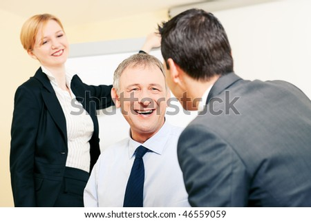 Small business team in the office in front of a whiteboard discussing something rather enjoyable, people are cheerful - stock photo