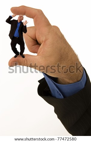Small businessman feeling the squeeze - stock photo