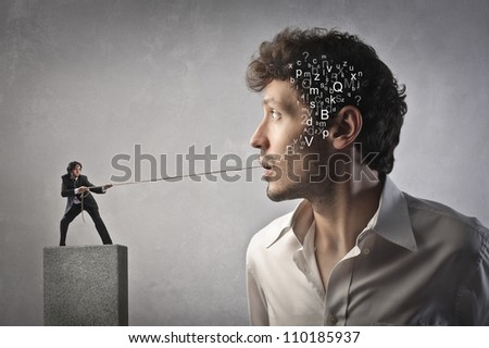 Small businessman pulling a rope and trying to pull out some alphabet letters from another man's mouth - stock photo