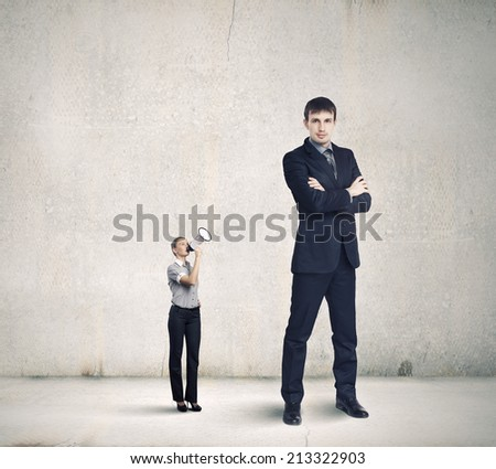 Small businesswoman screaming in megaphone on colleague of huge size - stock photo