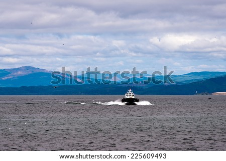Small but powerful pilot boat lift at the Astoria in the waters of the mouth of the Columbia River to the Pacific Ocean, bisecting the foaming waves on a background of mountains and blue haze. - stock photo