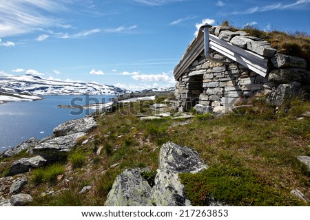 Small cabin above the lake in Norway - stock photo