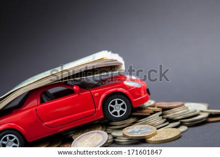Small car carrying many doolars, grey  background - stock photo