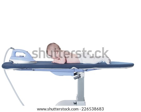 Small caucasian baby boy lying  on ironing system on the white background - stock photo
