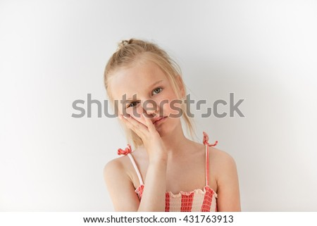 Small Caucasian girl looks tired in morning light indoors. Her facial expression shows boredom and indifference and her face resting on hand. All her appearance says «I don't care». - stock photo