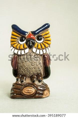 Small ceramic decorative owl  on grey background - stock photo