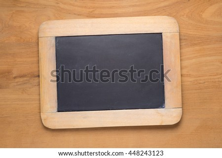 Small chalk blackboard on wooden desk, empty with room for copyspace text - stock photo