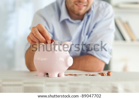 Small change being put into piggy bank - stock photo