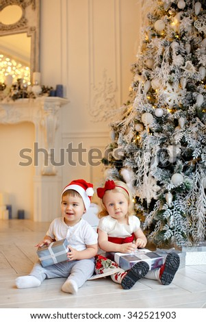 Small charming baby boy in red Santa hats and the little blond girl sitting at the Christmas trees and treat gifts, home interiors - stock photo
