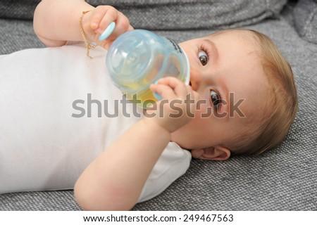 Small child - Baby sitting on sofa drinking - stock photo
