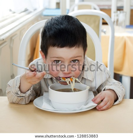Small child boy eating a soup in a restaurant. - stock photo