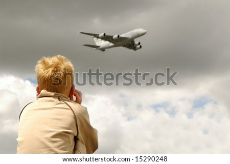 small child deafened by roar of a large jet aircraft overhead - stock photo