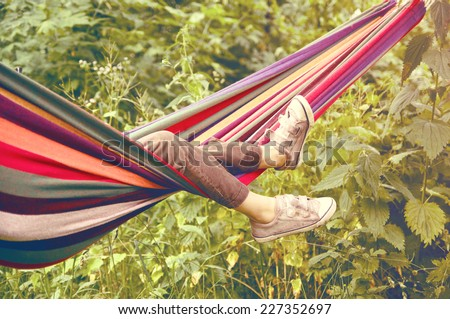 small child lying in a hammock in the woods - stock photo