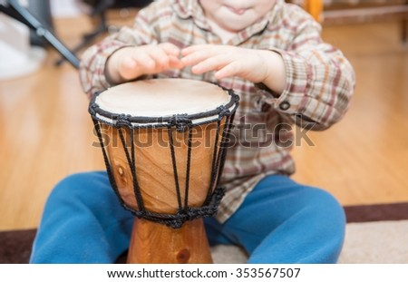 Small child playing on drum. Little caucasian boy and drum. Hands close up - stock photo